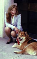 Valerie Bittner in light blue business suite knealing next to her dog Rocky, a red-sable Malamute